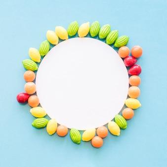 Biała kółkowa puste rama dekorująca z owoc kształtującymi cukierkami na błękitnym tle