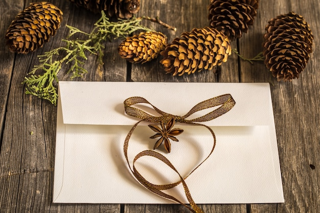 Biała koperta na drewnianej ścianie z szyszkami i prezentem świątecznym