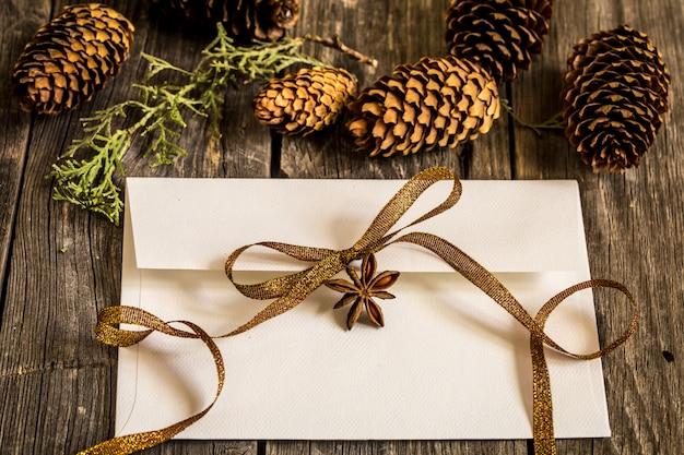 Biała koperta na drewnianej ścianie z szyszkami i świątecznym prezentem