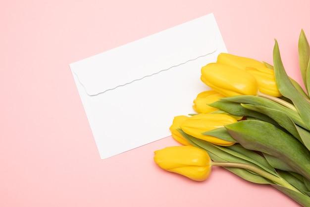 Biała koperta papierowa i żółte tulipany na różowym tle. romantyczna koncepcja świąteczna, dzień matki. makieta