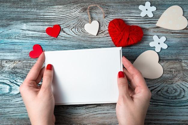 Biała koperta z pustym listem w rękach kobiety na romantycznym tle z sercami i