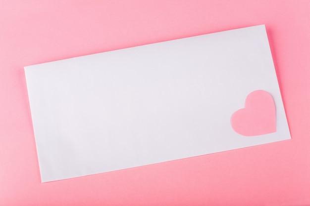 Biała koperta z różowym papierowym sercem i miejscem na tekst na różowym tle.