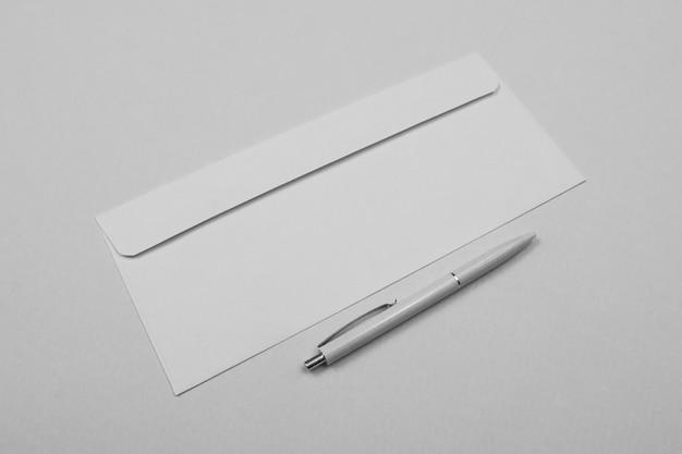 Biała koperta z wysokim kątem i długopis
