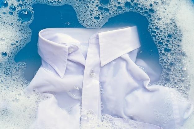 Biała koszula nasiąka rozpuszczonym detergentem w wodzie