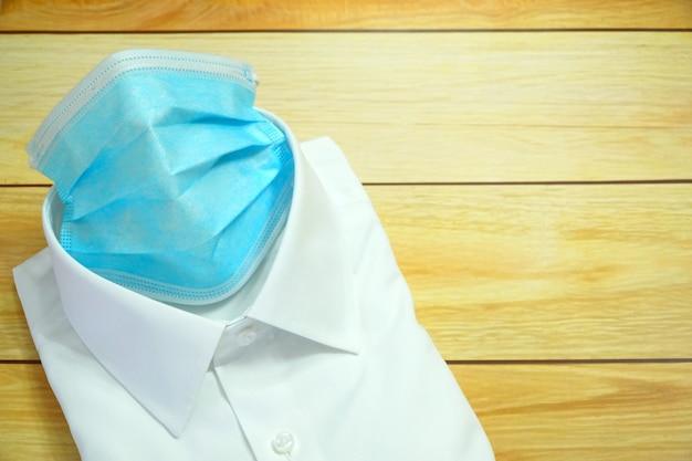 Biała koszula nosi chirurgiczną maskę na twarz, aby chronić bakterie koronawirusa (covid-19)