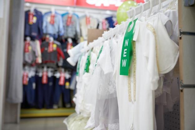 Biała koszulka dla dzieci na wieszakach w sklepie odzieżowym.