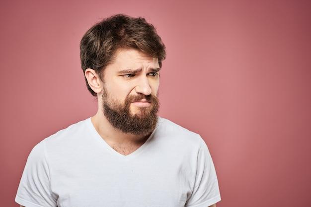Biała koszulka emocjonalnego mężczyzny smutny wyraz twarzy różowa ściana.