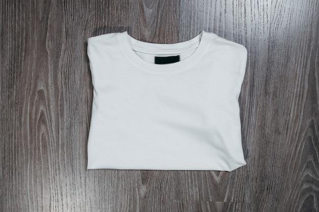 Biała koszulka na drewnianej przestrzeni