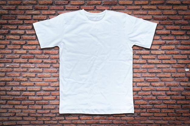 Biała koszulka na tle ściany z cegły.