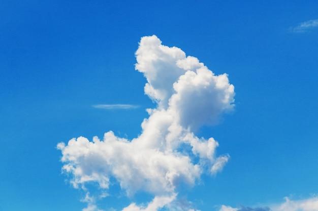 Biała kręcona chmura o dziwacznym kształcie na niebieskim niebie