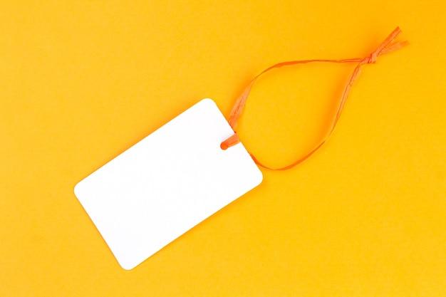 Biała księga pusta etykieta lub metka z ceną na pomarańczowym tle widok z góry