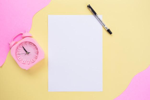 Biała księga z długopisem i budzikiem na żółtym i różowym tle. minimalistyczny styl