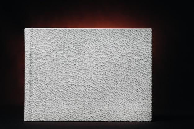 Biała księga z prawdziwej białej skóry na ciemnym tłoczonym tle. biała księga na ciemnym tle.