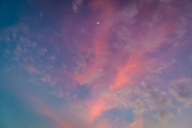 Biała księżyc na kolorowym żywym różowym i błękitnym mrocznym niebie.
