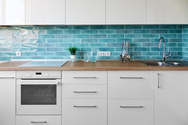 Biała kuchnia w nowoczesnym stylu z akcesoriami kuchennymi na tle niebieskich płytek