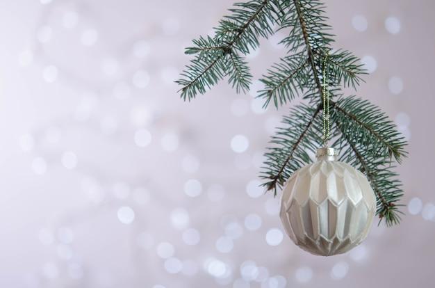 Biała kula wisi na gałęzi choinki. bokeh. dekoracja świąteczna