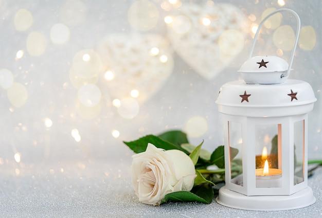 Biała latarnia i róża na srebrnym tle bokeh.