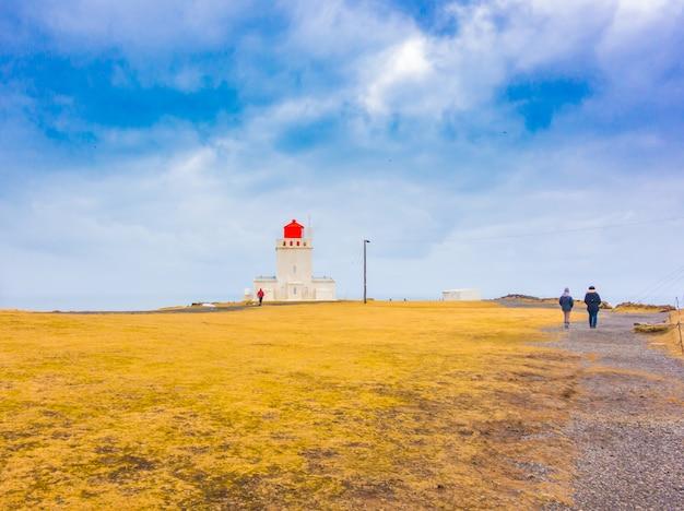 Biała latarnia morska na cape dyrholaey, islandia. .