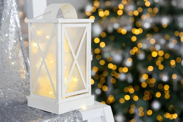 Biała latarnia stoi na cekinowej tkaninie na tle świateł girlandy