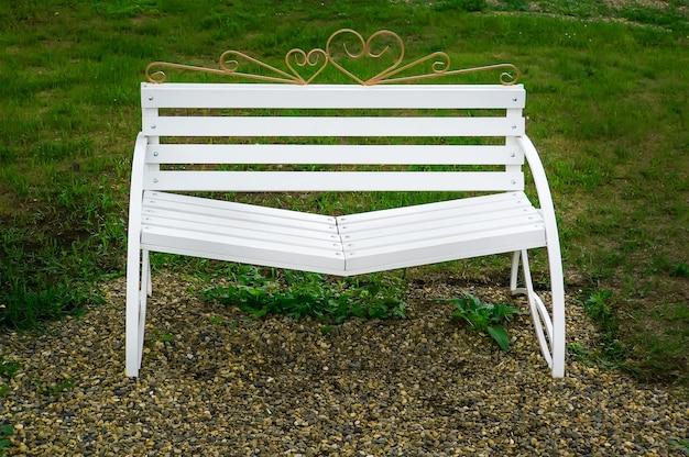 Biała ławka pogodzenia z pochyłymi siedzeniami w parku na tle ogrodu.