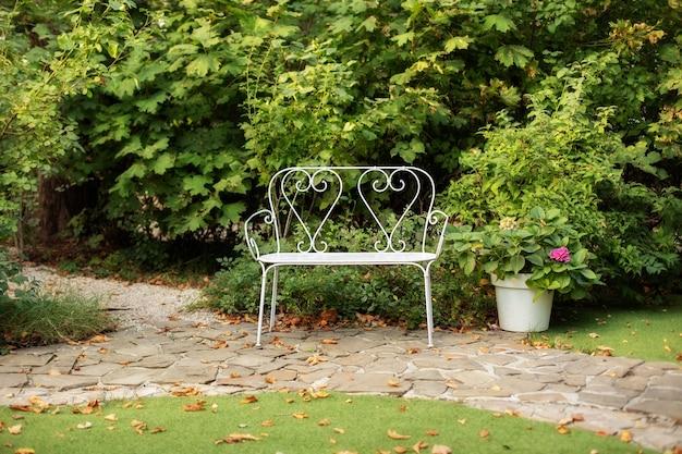 Biała ławka w letnim ogrodzie do wypoczynku