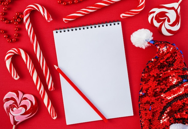 Biała lista życzeń pusta z cukierkami i czapką mikołaja na czerwonym tle