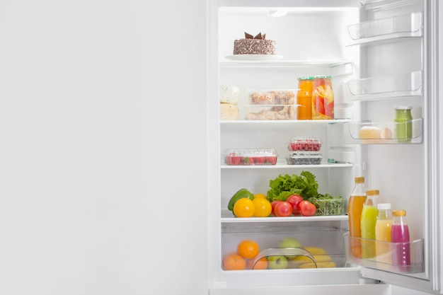 Biała lodówka z różnymi potrawami