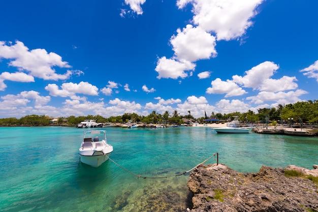 Biała łódź blisko skalistego brzeg w bayahibe, los angeles altagracia, republika dominikańska.