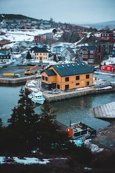 Biała łódź na wodzie w pobliżu domów w ciągu dnia