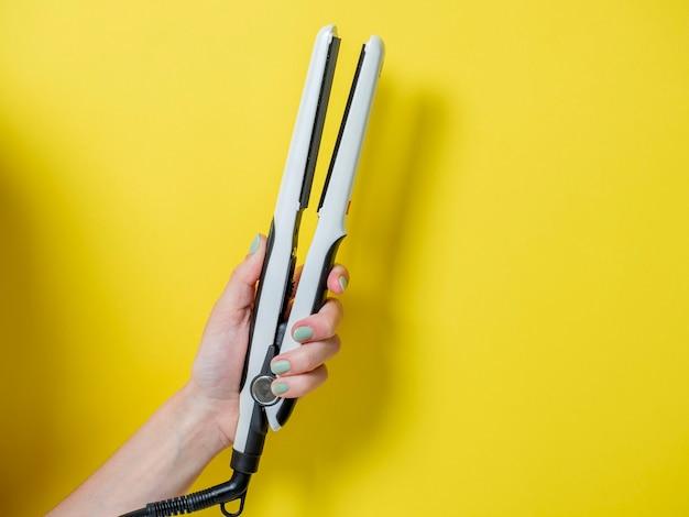 Biała lokówka w kobiecej dłoni na żółtym tle. akcesorium do tworzenia fryzur. uroda i moda. pielęgnacja włosów.