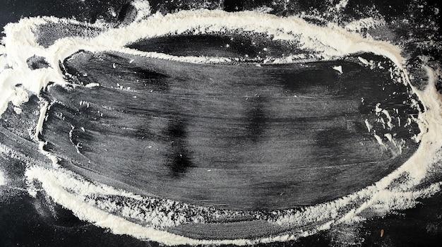 Biała mąka pszenna rozrzucona na czarnym stole