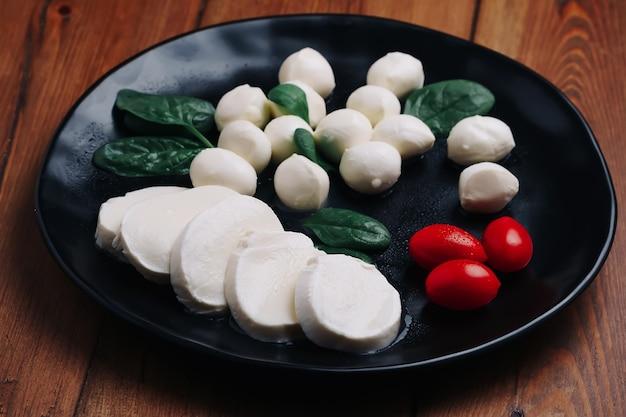 Biała mała mozzarella, kulki serowe, liście szpinaku i pomidory na czarnym talerzu