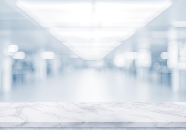 Biała marmurowa powierzchnia na zamazanym pustym biurze