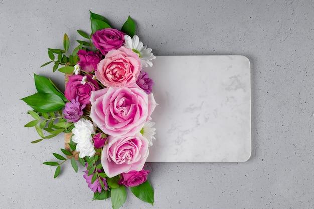 Biała marmurowa ramka ozdobiona pięknymi letnimi kwiatami z pustym miejscem na tekst różowe róże i