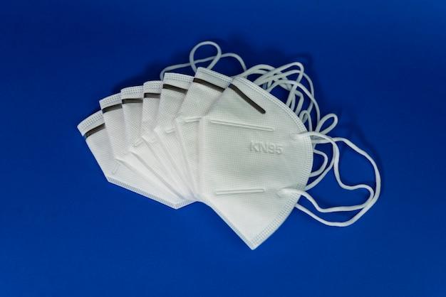 Biała maska kn95 lub n95 z antywirusową maską medyczną do ochrony przed koronawirusem na niebiesko