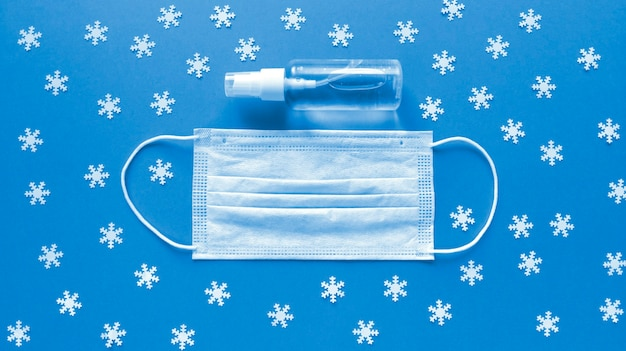 Biała maska medyczna i środek dezynfekujący do rąk w przezroczystej butelce z nasadką sprayu na środku niebieskiego tła i rozrzuconymi białymi płatkami śniegu. prosty świąteczny układ płaski. pojęcie medyczne. zdjęcie stockowe.