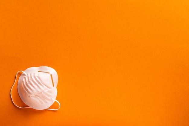 Biała maska medyczna na pomarańczowym tle
