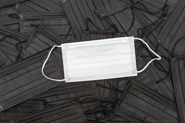 Biała maska medyczna na tle rozproszonych czarnych masek medycznych