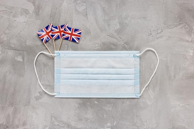 Biała maska medyczna usta i flagi wielkiej brytanii na szarym tle. mutacja koronawirusa covid-19 w wielkiej brytanii, koncepcja blokady, kwarantanny i podróży. przestrzeń płaska świeckich kopii