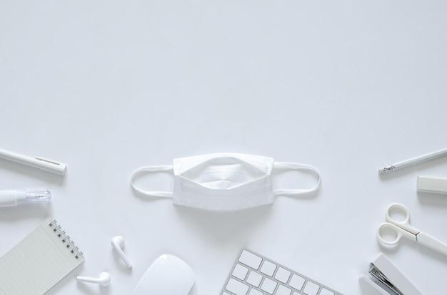 Biała maska ze szkolnymi i biurowymi materiałami piśmiennymi na białym tle na powrót do szkoły i nową normalną koncepcję.