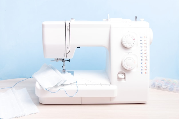 Biała maszyna do szycia, maseczka na twarz z tkaniny w domu, niebieska ściana
