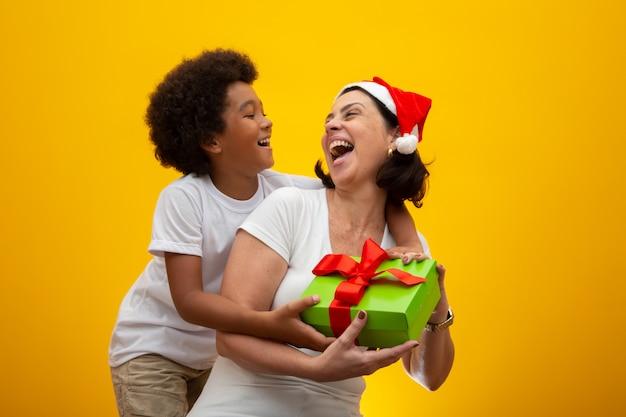 Biała matka z czarnym synem wymienia prezenty w wigilię bożego narodzenia. przybrane dziecko szacunek społeczny, kolor skóry, włączenie.