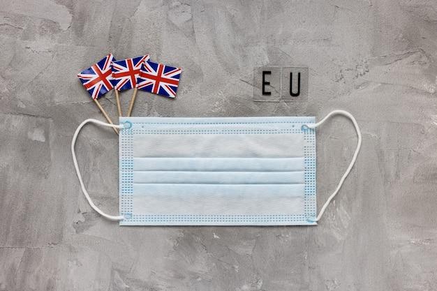 Biała medyczna maska na usta flagi wielkiej brytanii i znak ue na szarym tle koronawirus covid muta...