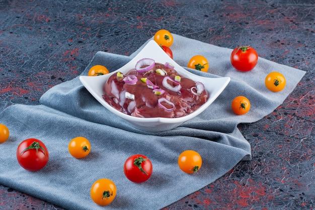Biała miska kawałków mięsa z pomidorami cherry na tle marmuru.
