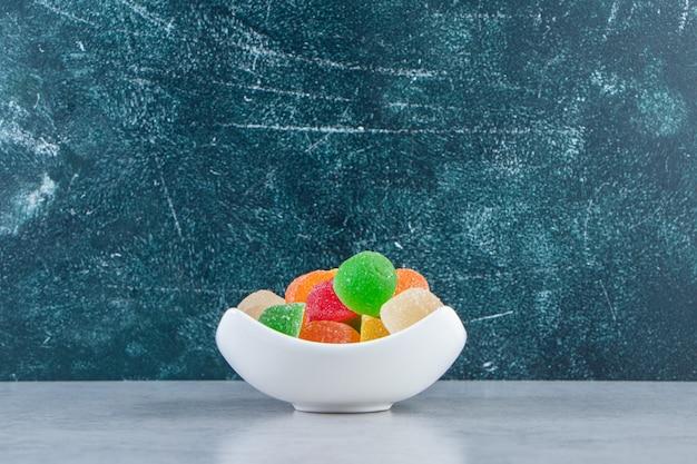 Biała miska kolorowych marmolad galaretki na marmurowym tle.