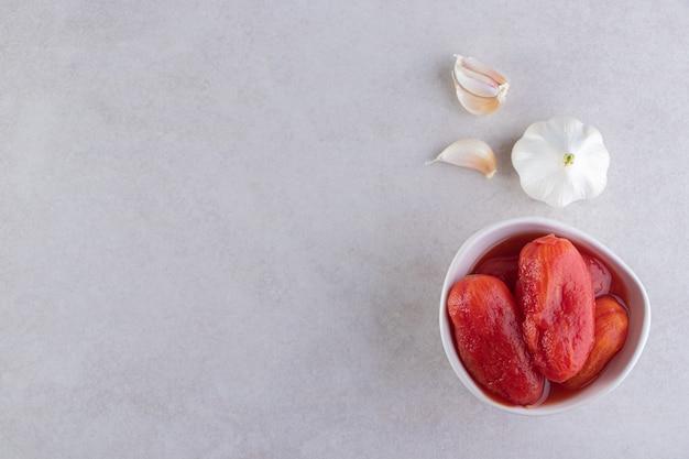 Biała miska marynowanych pomidorów umieszczona na kamiennym stole.