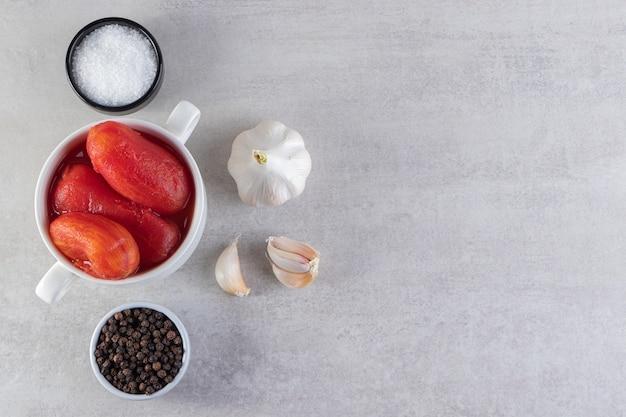 Biała miska marynowanych pomidorów umieszczona na kamiennym tle.