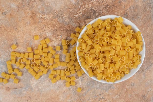 Biała miska nieprzygotowanego makaronu na marmurowym tle