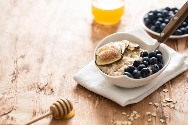 Biała miska owsianej figi i jagód.