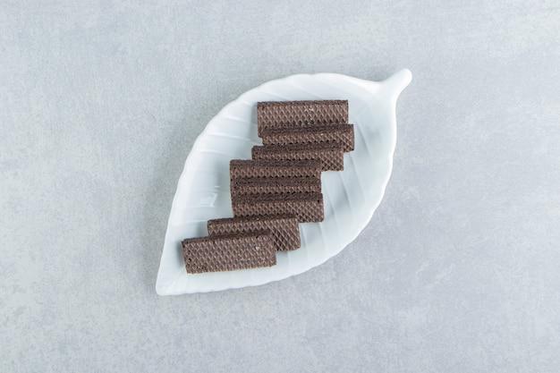 Biała miska pełna czekoladowych gofrów.